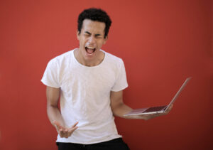 man showing frustration while holding a laptop